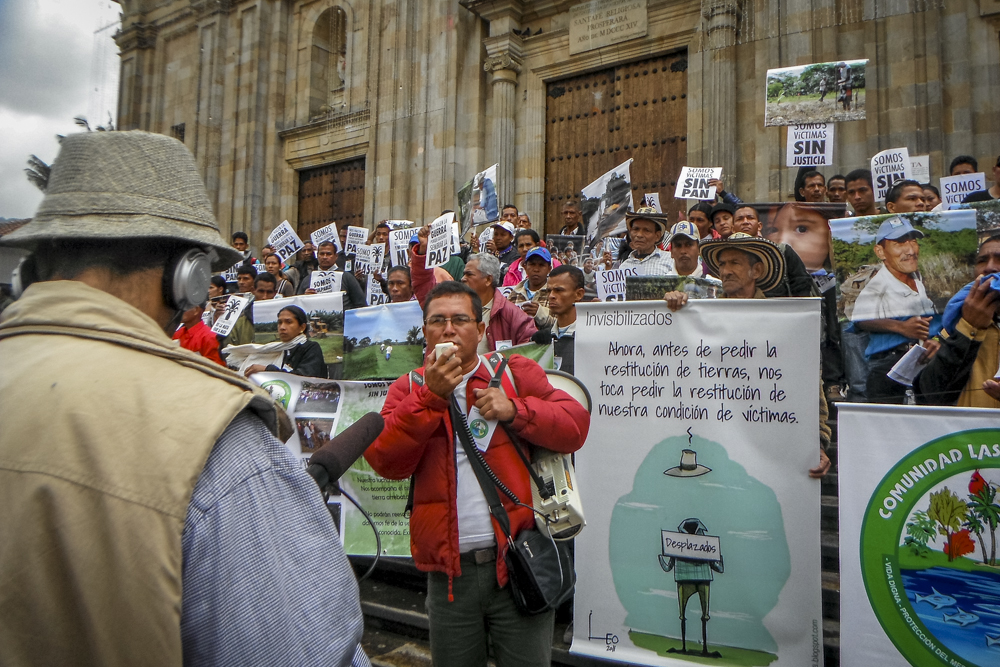 "Farmers demonstrate at Parque Bolivar, Bogotá. The sign reads, ""Now, before asking for the restitution of land, we have to ask for the restitution of our condition as victims."""